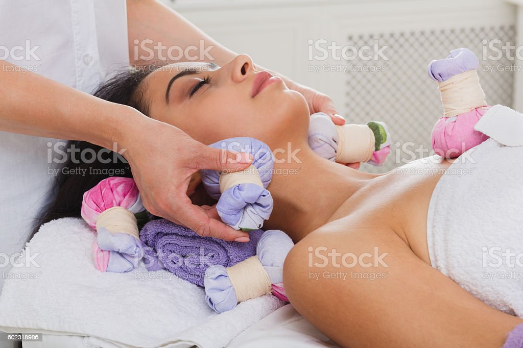Woman has herbal ball massage in ayurveda spa wellness center stock photo