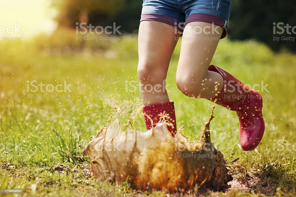Woman have fun jumping in puddle stock photo