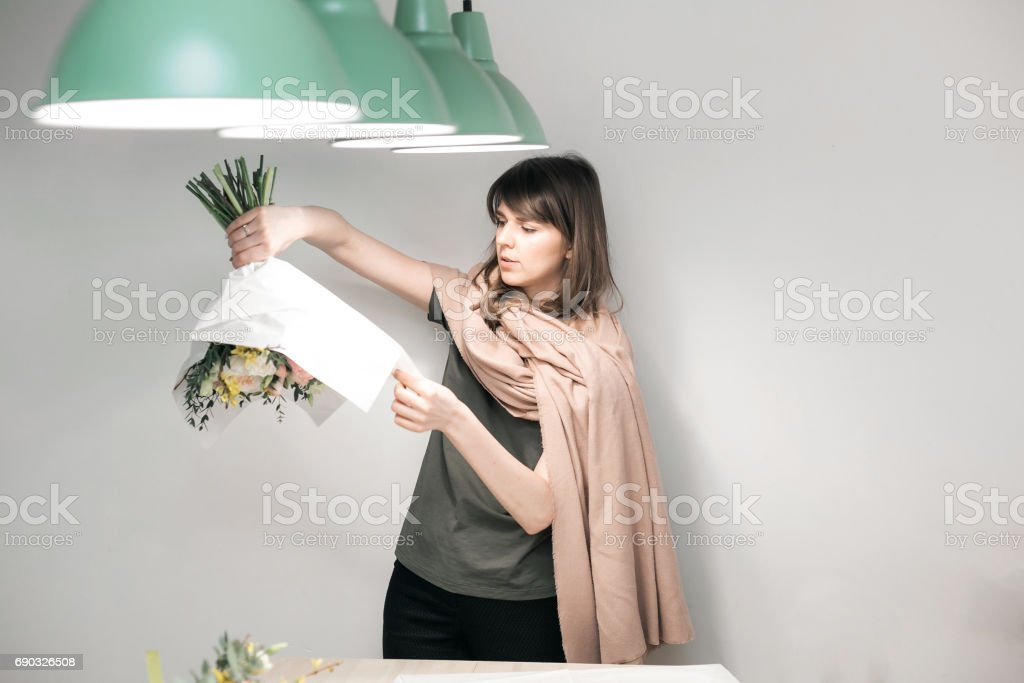 Woman have pack festive bouquet in wrapping paper. Young beautiful florist make floristry assemble with pink peony and wildflowers in workshop on gray background stock photo