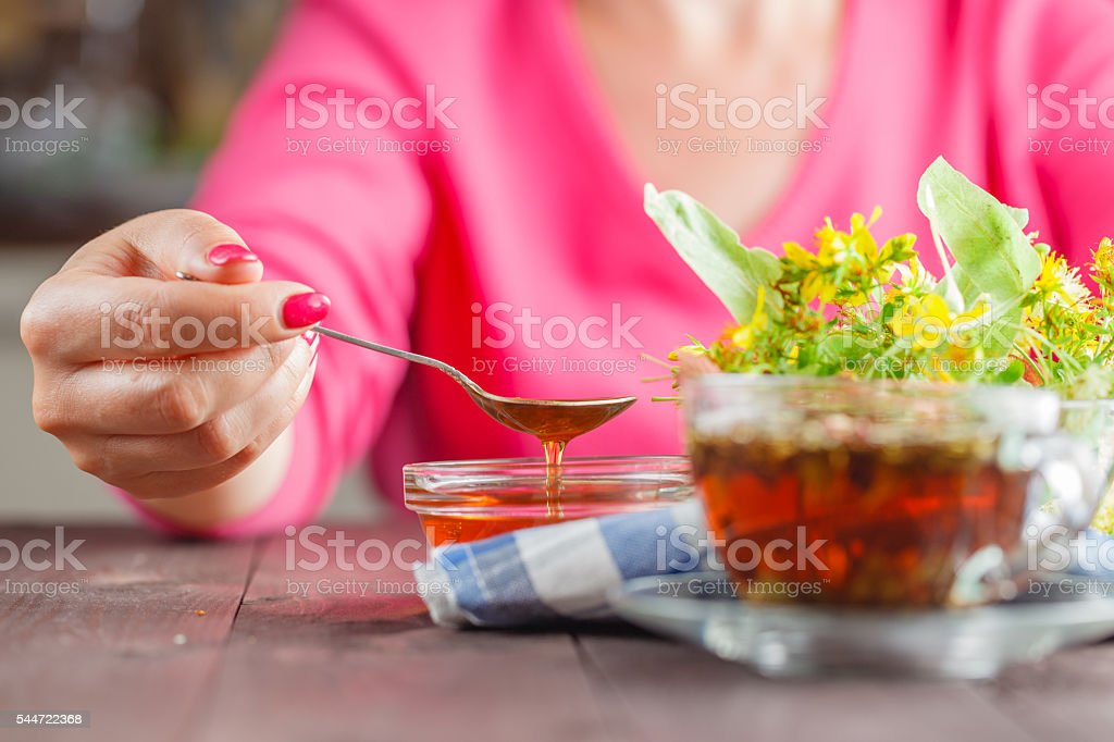 Woman have scooped the spoon of honey on wooden table stock photo
