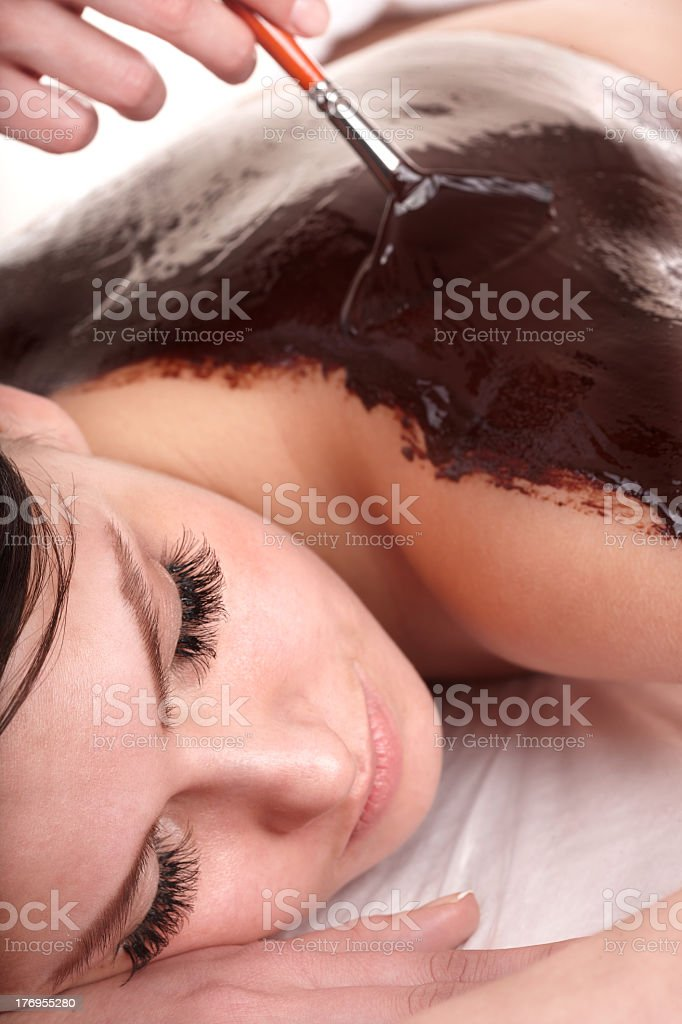 Woman having a chocolate body mask done stock photo