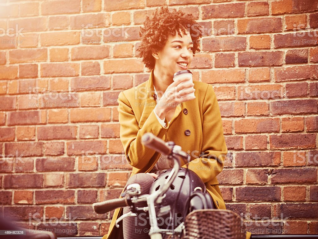 Woman having a coffe on the street bench stock photo