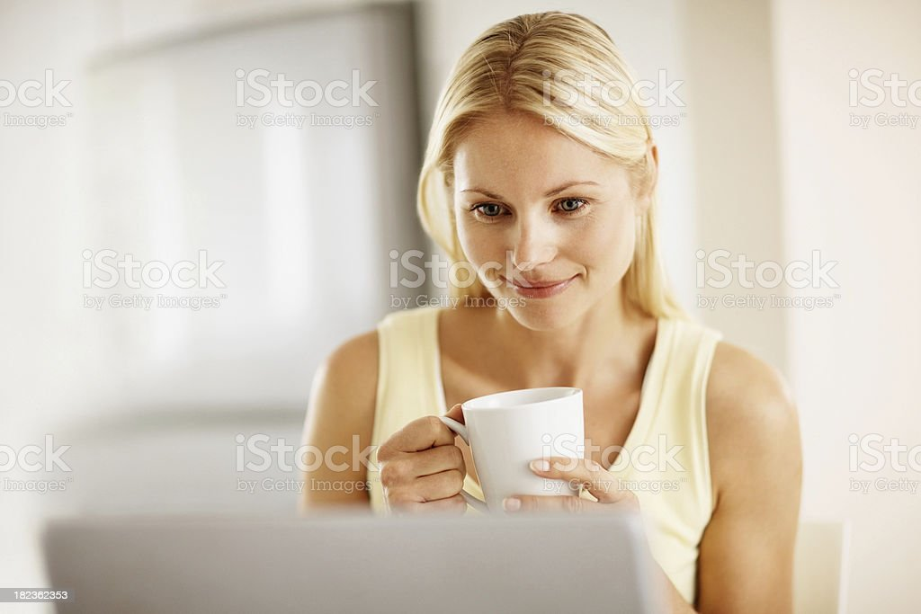 Woman having a cup of coffee and working on laptop royalty-free stock photo