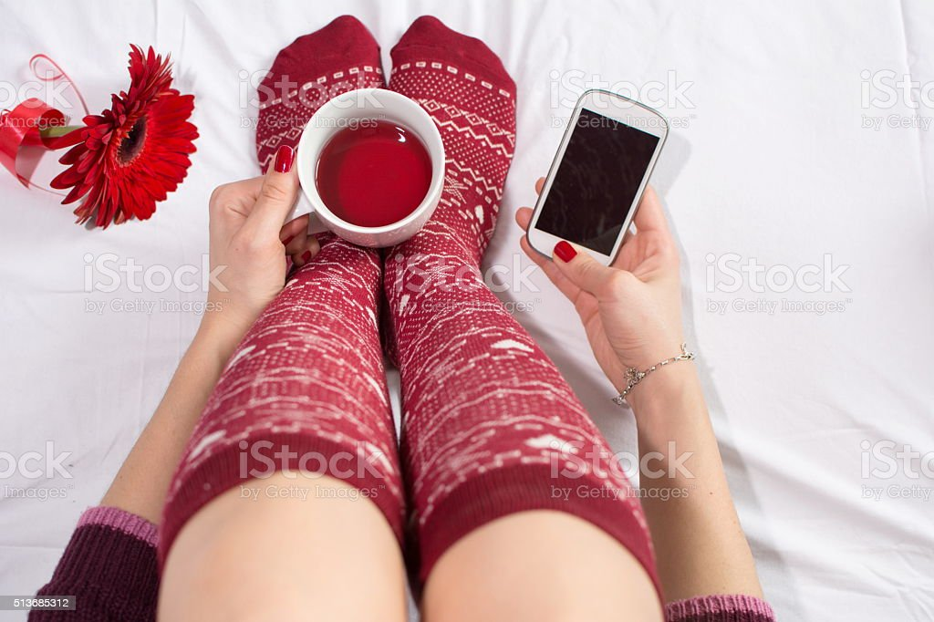 Woman having a cup of tea and texting stock photo