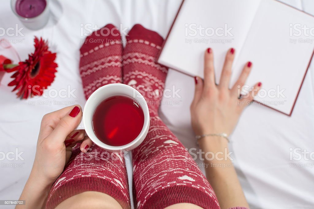 Woman having a cup of tea in bed stock photo