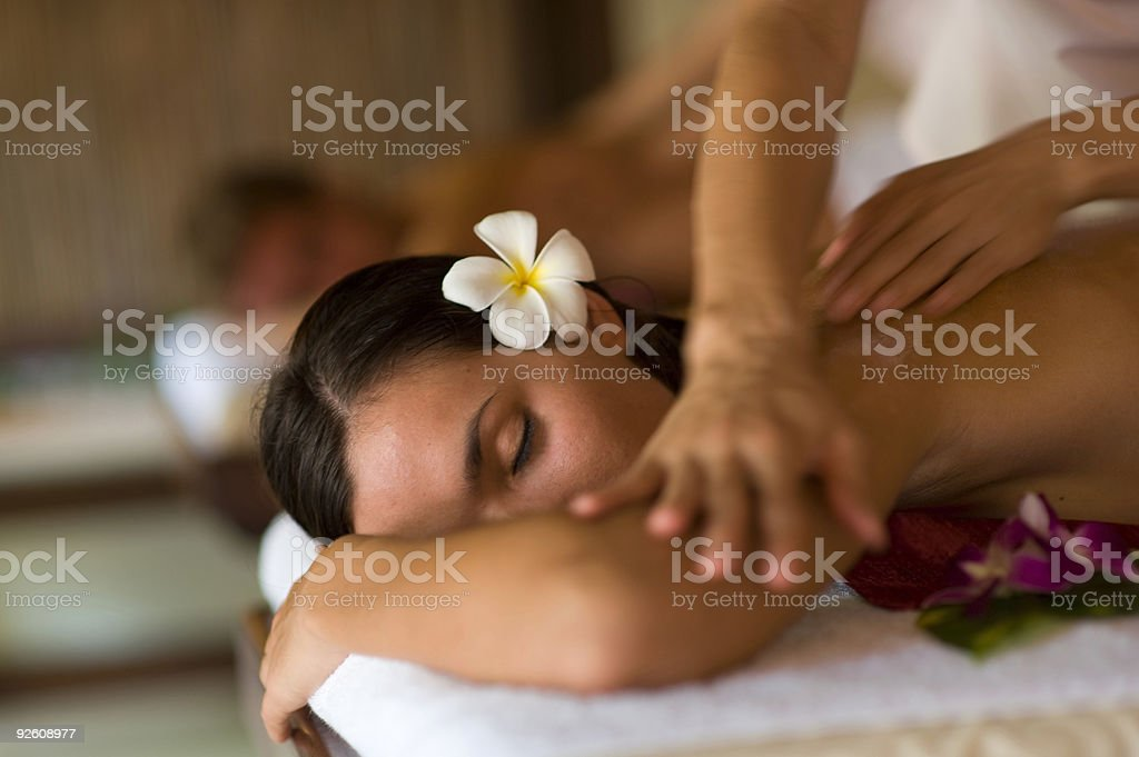 A woman having a massage with a flower in her hair stock photo