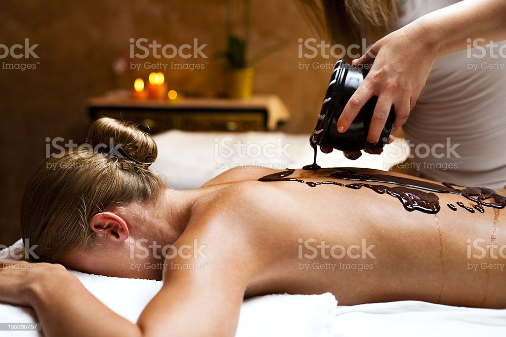 Woman having a massage with hot chocolate stock photo