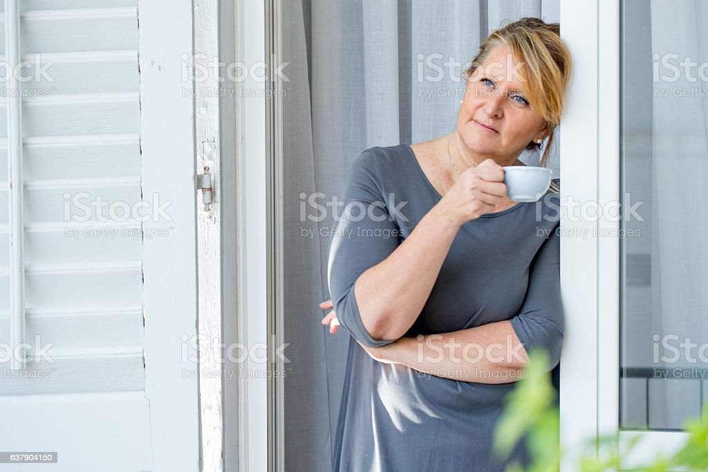 Woman having a morning Coffee on the Balcony stock photo