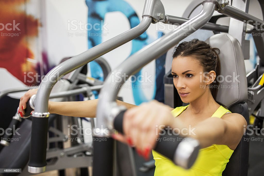 Woman having a sports training on exercise machine at gym. stock photo