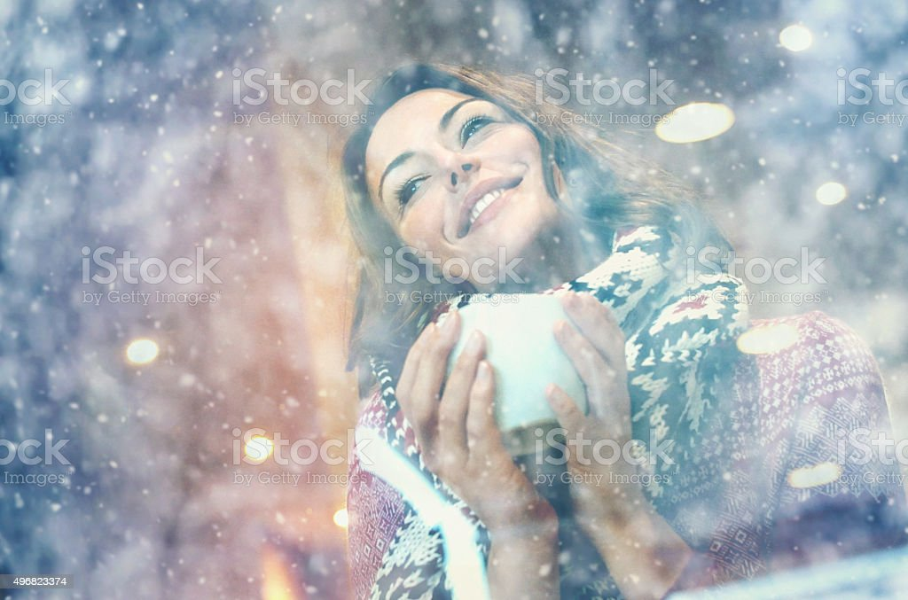 Woman having a tea or coffee on snowy day. stock photo