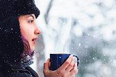 Woman having a tea or coffee on snowy day