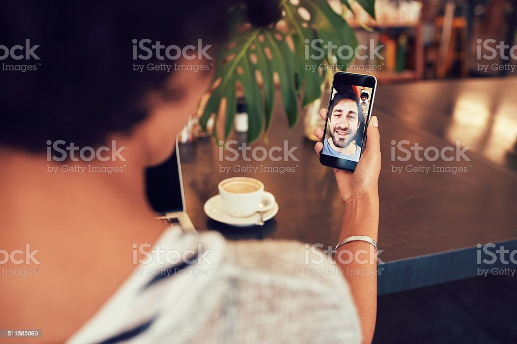 Woman having a videochat with friend on mobile phone. stock photo