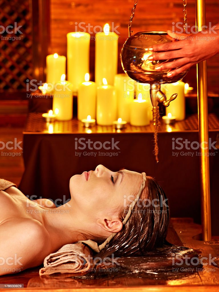 A woman having an Ayurvedic spa treatment with candles lit stock photo