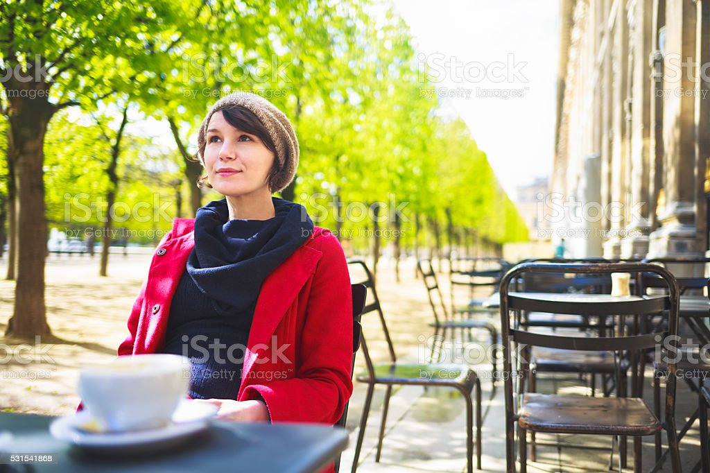 Woman having coffee in parisian cafe in park. stock photo