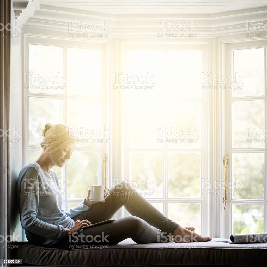 Woman having coffee while using digital tablet on window sill stock photo