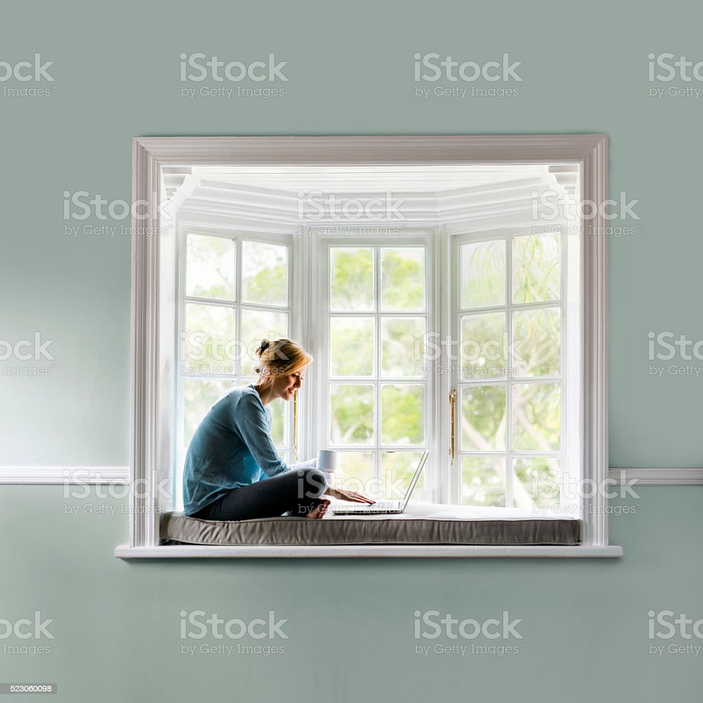 Woman having coffee while using laptop on window sill stock photo