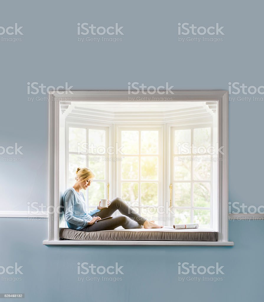 Woman having coffee while using tablet PC on window sill stock photo
