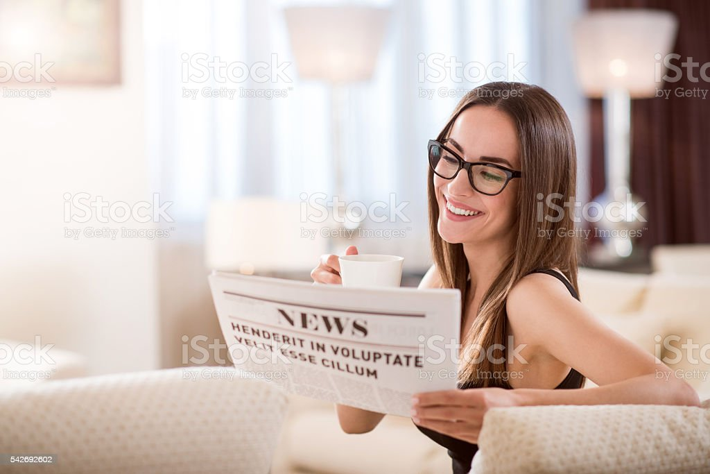 Woman having drink and reading news stock photo