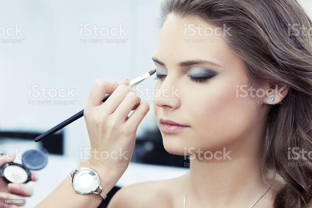 Woman having eye shadow applied stock photo