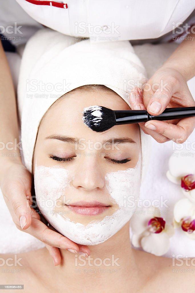 Woman having facial mask at beauty salon stock photo