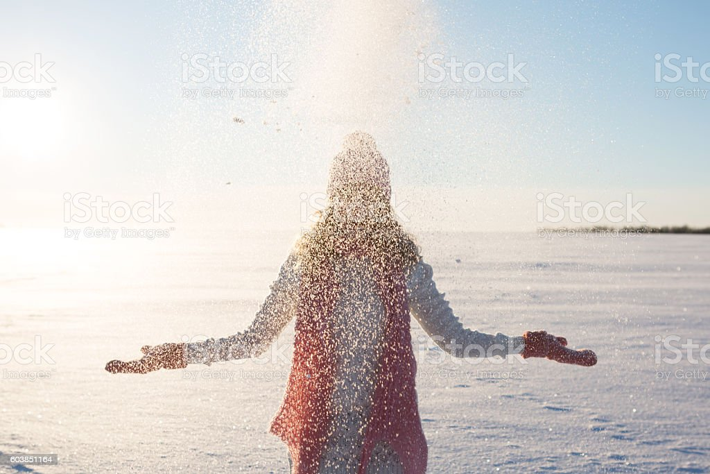 Woman having fun and throwing snow in winter field stock photo