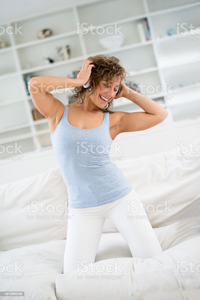 Woman having fun listening to music at home stock photo