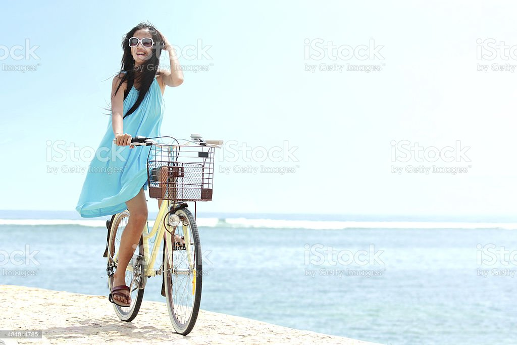 woman having fun riding bicycle at the beach stock photo