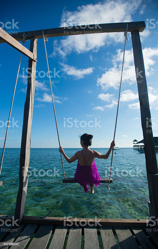 woman having fun swinging ,Malaysia, Semporna stock photo