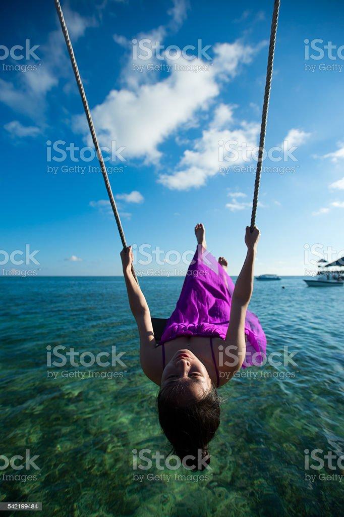 woman having fun swinging ,Malaysia, Semporna stock photo