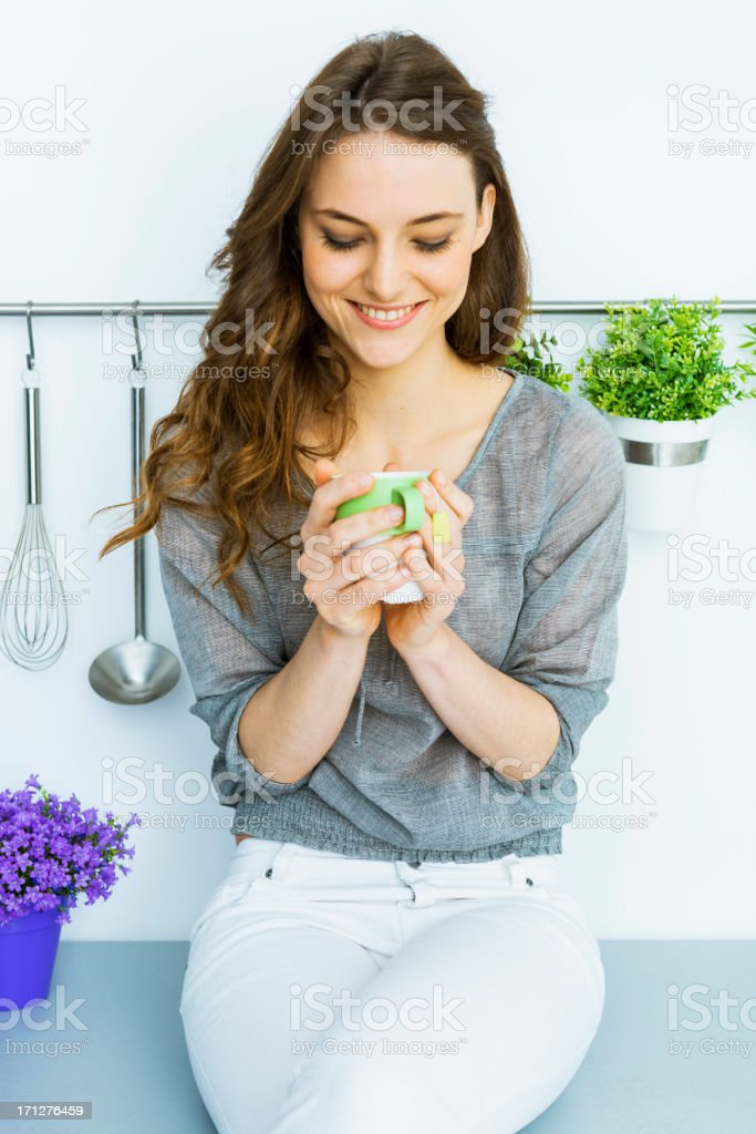Woman having green tea in her loft stock photo