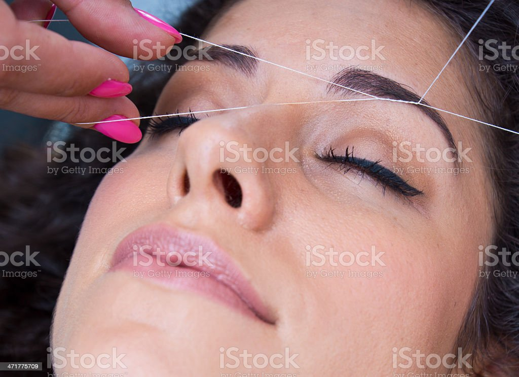 A woman having her eyebrows threaded stock photo