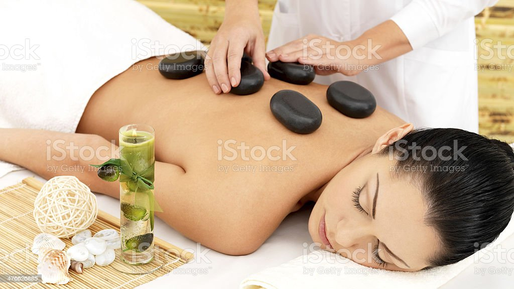 Woman having hot stone massage of back in spa salon royalty-free stock photo