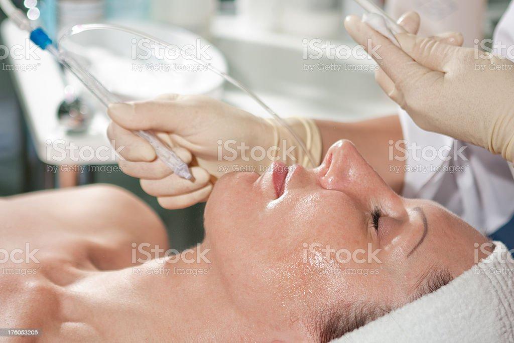 Woman having jet peeling facial treatment royalty-free stock photo