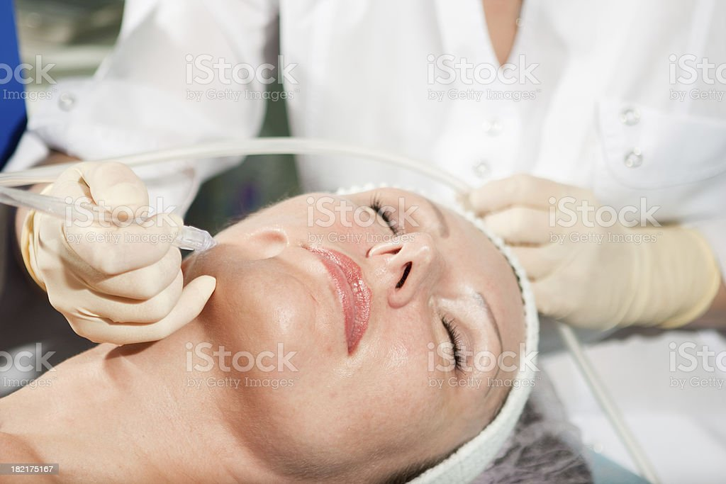 Woman having jet peeling facial treatment royalty-free stock photo
