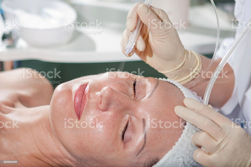 Woman having jet peeling facial treatment stock photo