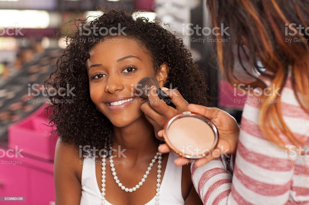 Woman having makeup applied. stock photo