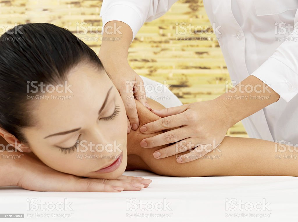 Woman having massage of body in spa salon stock photo