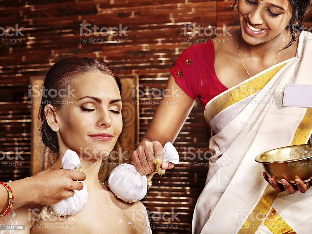 Woman having massage with pouch of rice. stock photo