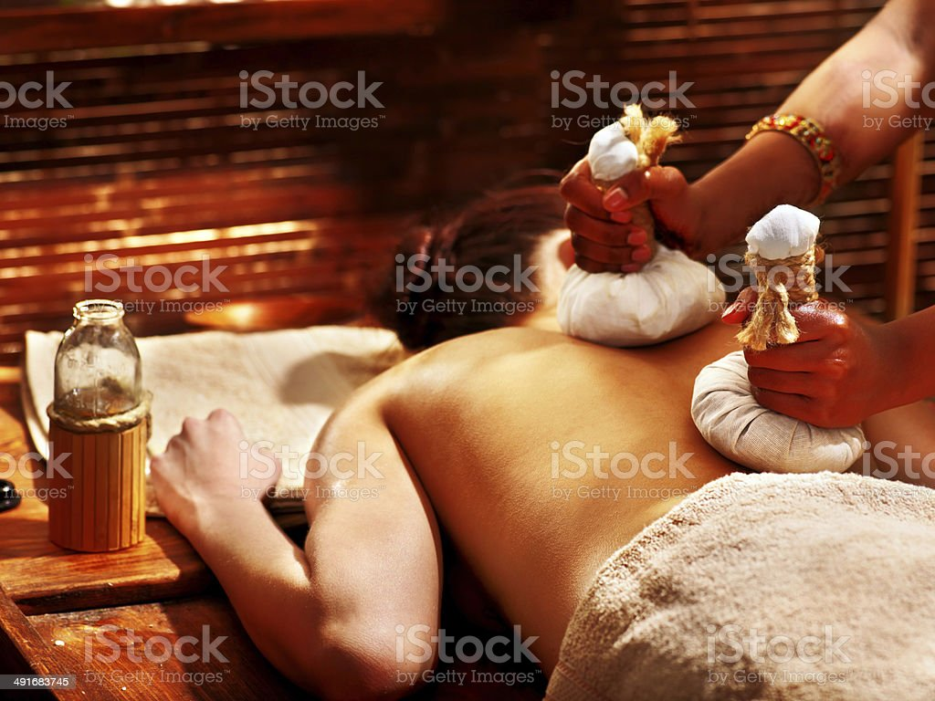 Woman having massage with pouch. stock photo