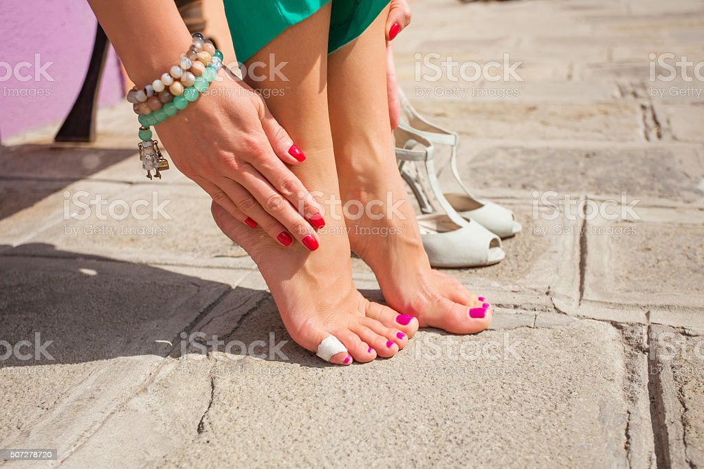 Woman having painful feet due to unfit shoes stock photo