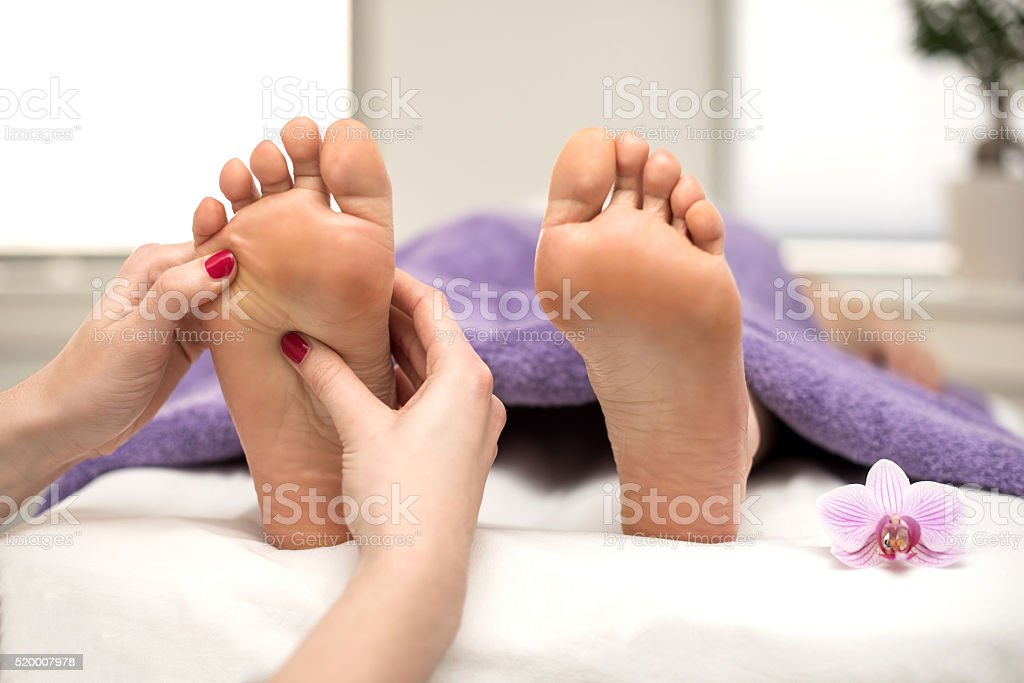Woman having pedicure treatment at spa or beauty salon with stock photo