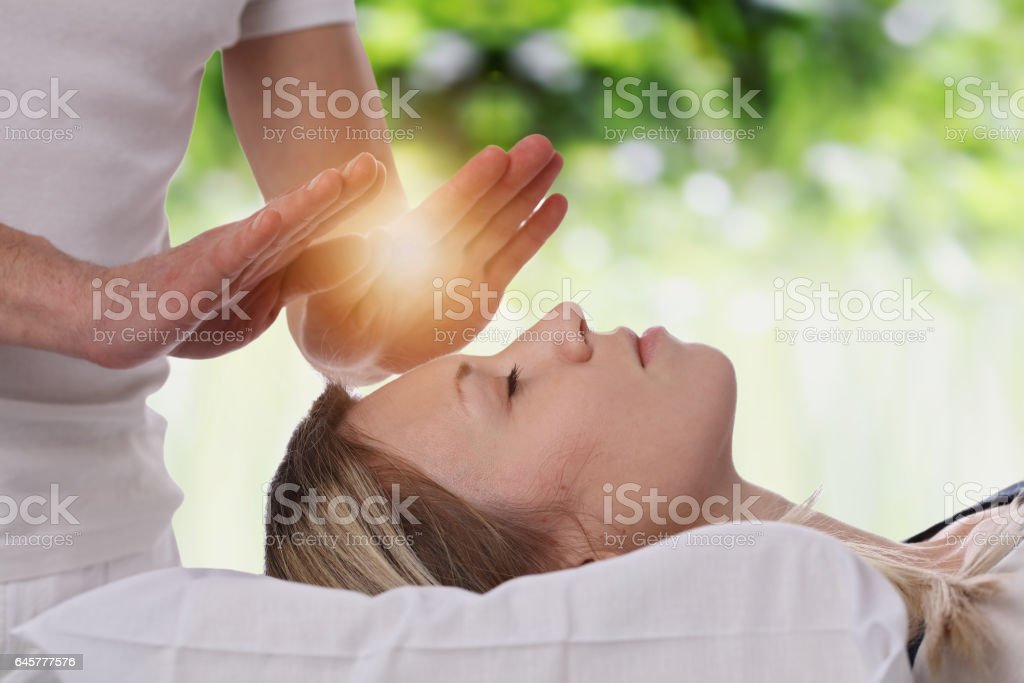 Woman having reiki healing treatment , alternative medicine concept. stock photo