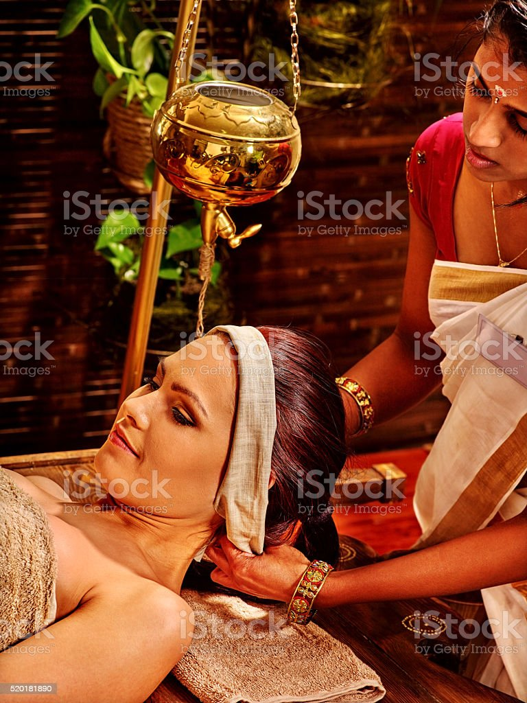 Woman having Shirodhara pouring oil on head in India spa stock photo