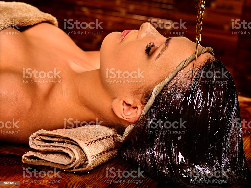 Woman having Shirodhara pouring oil on head in India spa . stock photo