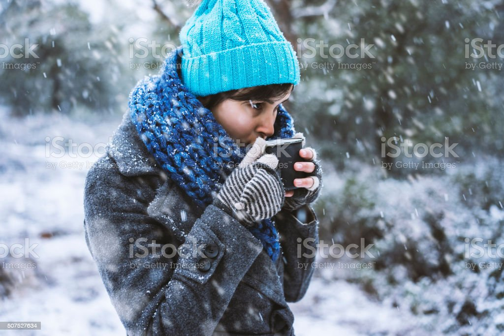 Woman having tea or coffee in a snowy day stock photo