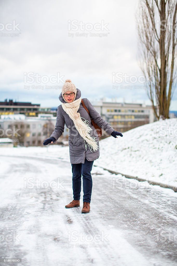 Woman having troubles walking on an icy footpath stock photo