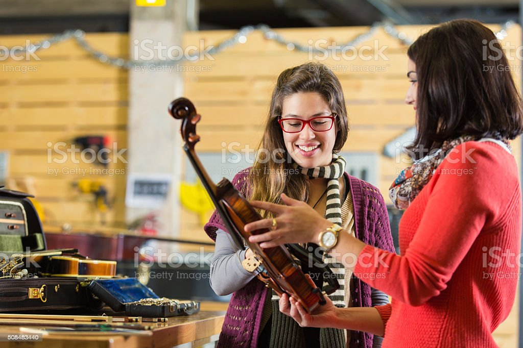 Woman having violin repaired in music store stock photo