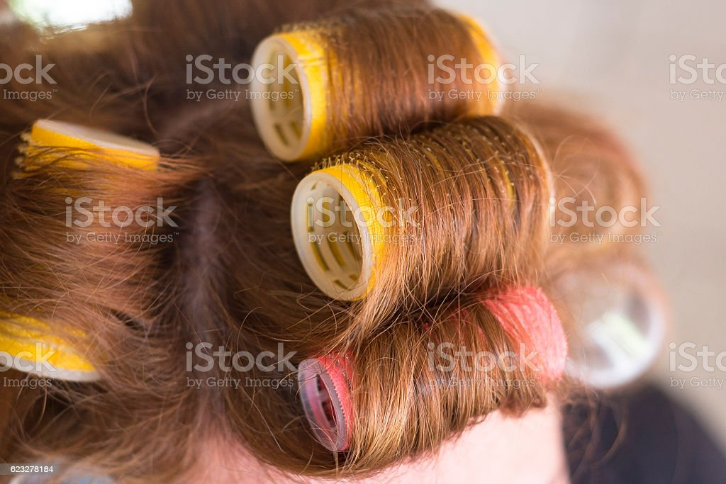 Woman head with hair curlers rollers stock photo