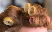 Woman head with hair curlers rollers