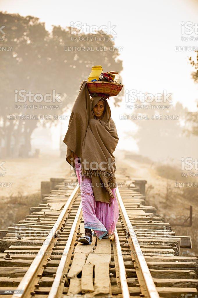Woman heading stuff walking on the railway in misty morning stock photo